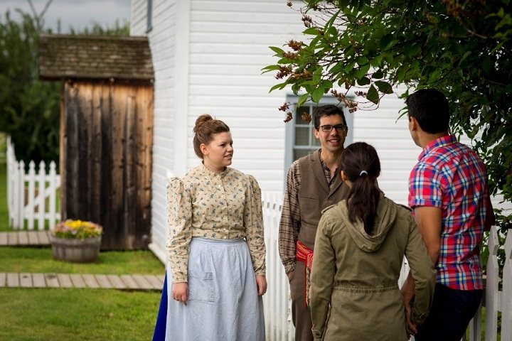 Period costumed staff talking with visitors