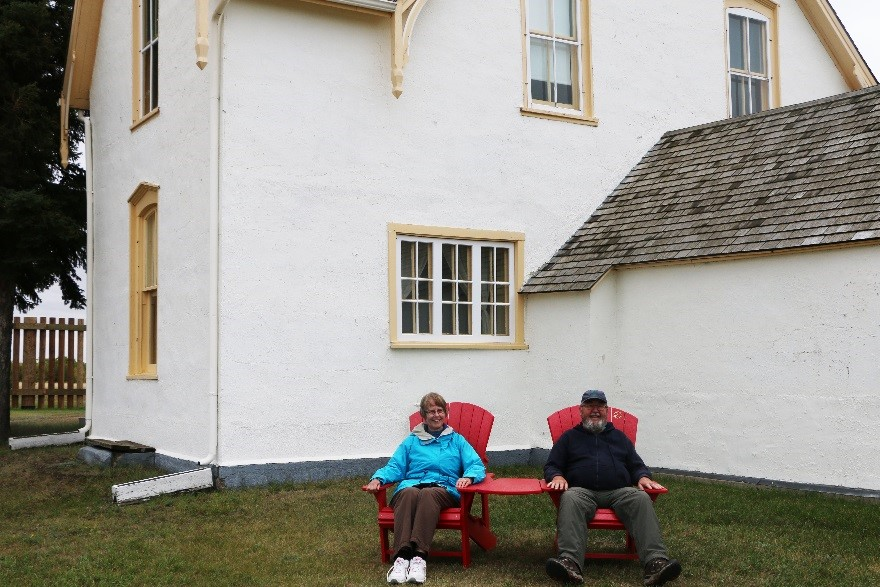 Visitors to Fort Battleford can enjoy the view from the Parks Canada's red chairs
